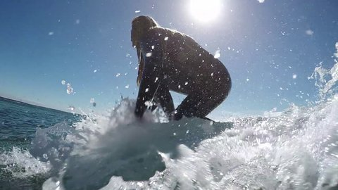 SLOW MOTION UNDERWATER: Young surfer girl surfing on a wave and splashing pass the camera in beautiful Atlantic ocean in Canary island