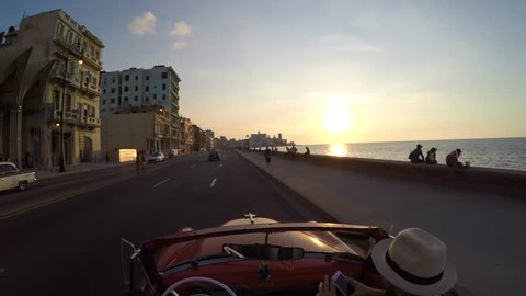 Driving classic convertible car wIth sunset in Havana, Cuba