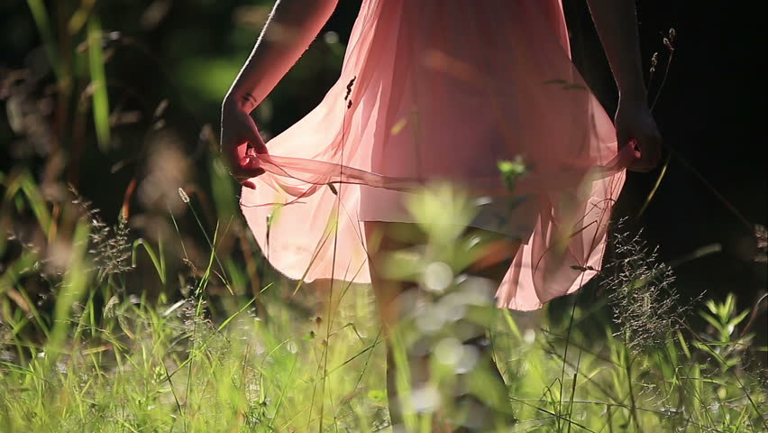 Girl Wearing Light Summer Dress Walking in the Field on Sunny Day Outdoors #10958423