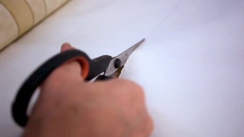 Woman's hand cutting wallpaper during repairs. HD. 1920x1080