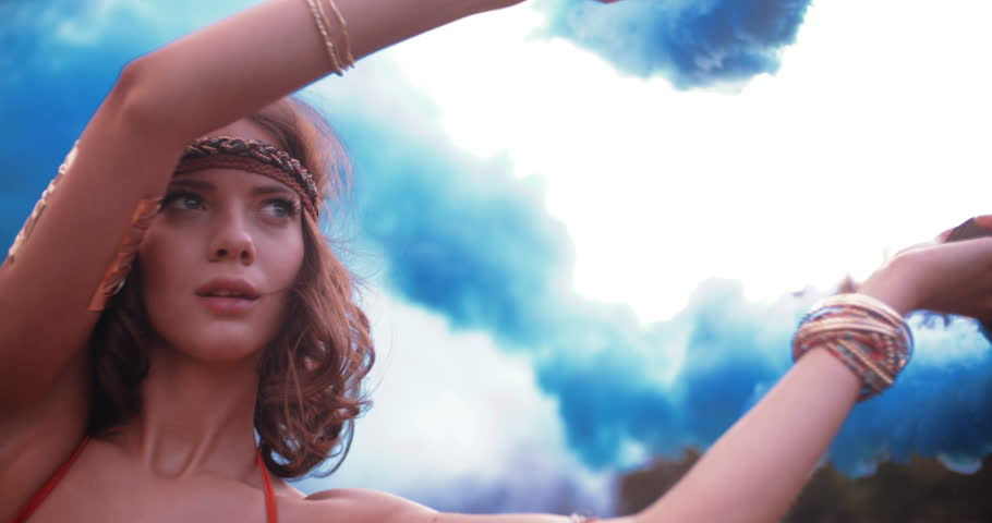 Boho girl turning her arms with blue smoke flares in nature in Slow Motion