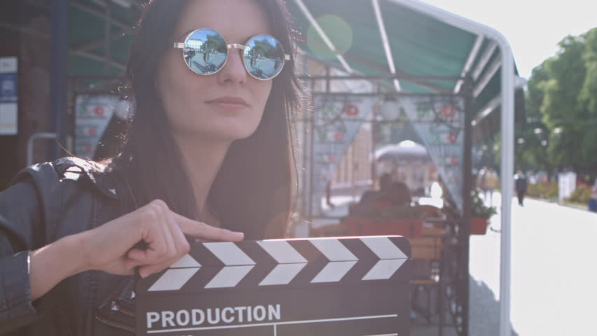 Beautiful girl with a clapperboard on the streets