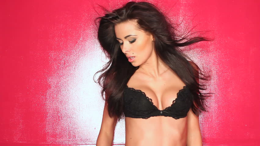Charming woman in black sexy lingerie posing on red background