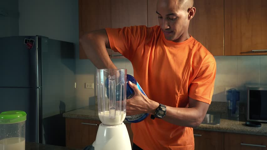 Young african american man in domestic kitchen, preparing a milk shake with proteins and vitamins. Black guy pours proteic supplement into the blender