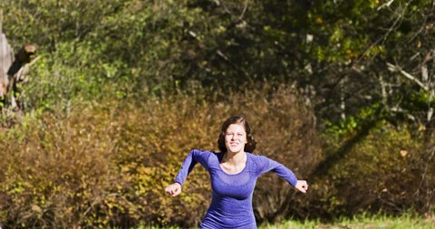 Beautiful young woman jumping, laughing, and kicking up her heels in slow motion in a woodland setting