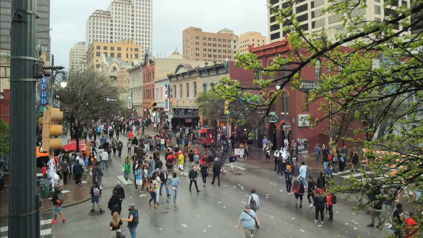AUSTIN, TEXAS CIRCA MARCH 2015.  Time lapse shot of 6th Street in Austin, texas during SXSW 2015 at dusk on a windy rainy day. The One American center building is in the background.