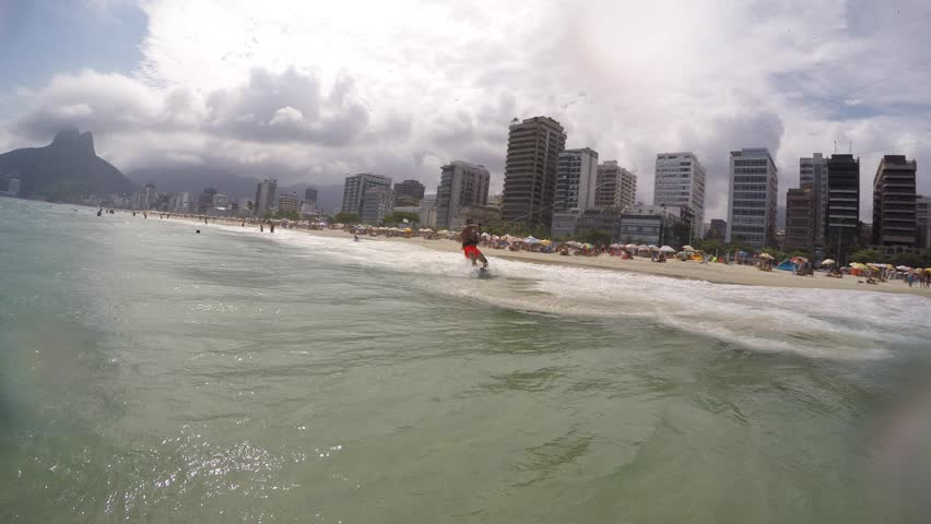 IPANEMA BEACH, BRAZIL - FEBRUARY 2015: A kiteboarder races past  GoPro Hero4 camera as he heads out into the ocean. He does a flip on the kiteboard at end of clip. POV GoPro Hero4 3840x2160 UltraHD.