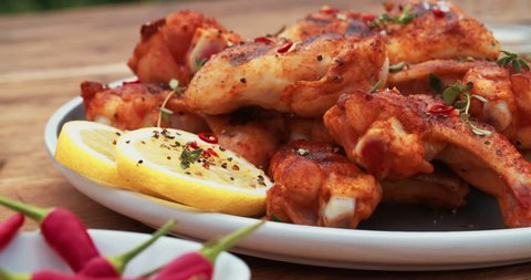 Plate of tempting spicy chicken wings with lemon slices on a wooden table with condiments in the background
