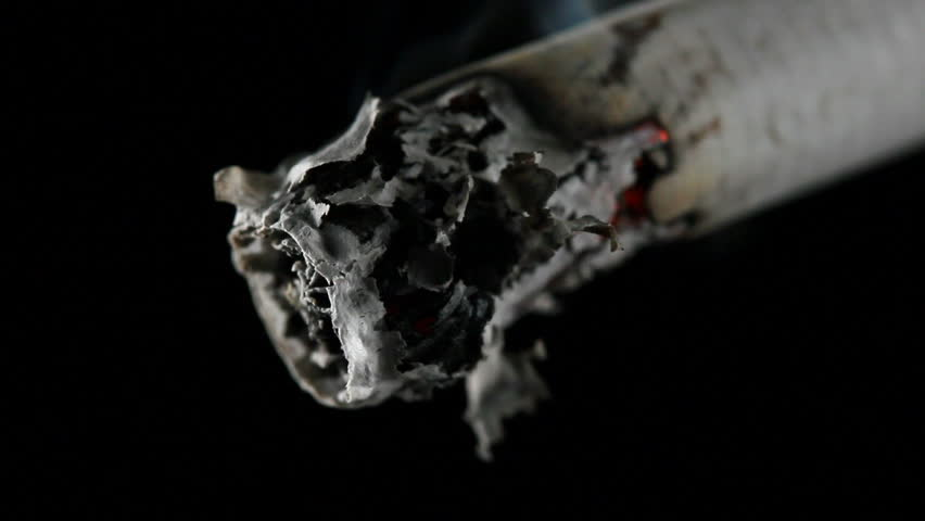 Closeup of a cigarette burning with smoke flowing up into the darkness