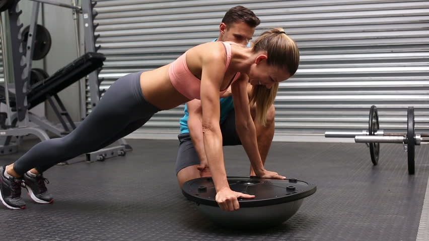 Fit woman doing bosu press up with trainer at a crossfit gym