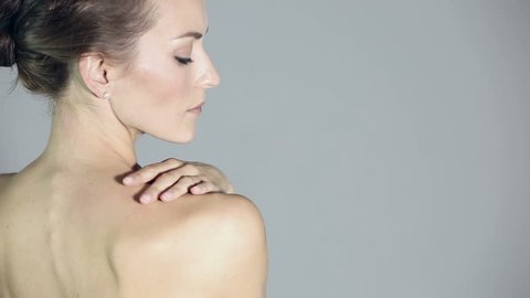 Woman massaging her neck and shoulder from an ache or pain with her back to camera