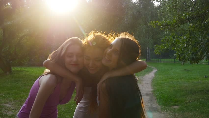 Three friends, young girls, having fun strolling in park, hugging, laughing.  Sunset,  backlight, slow motion, medium shot. #11164853