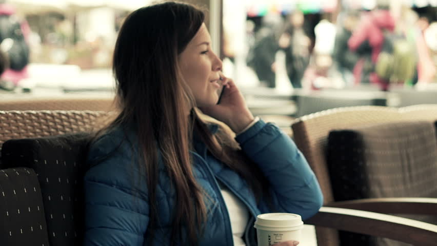 Young, pretty woman talking on cellphone sitting in cafe in city