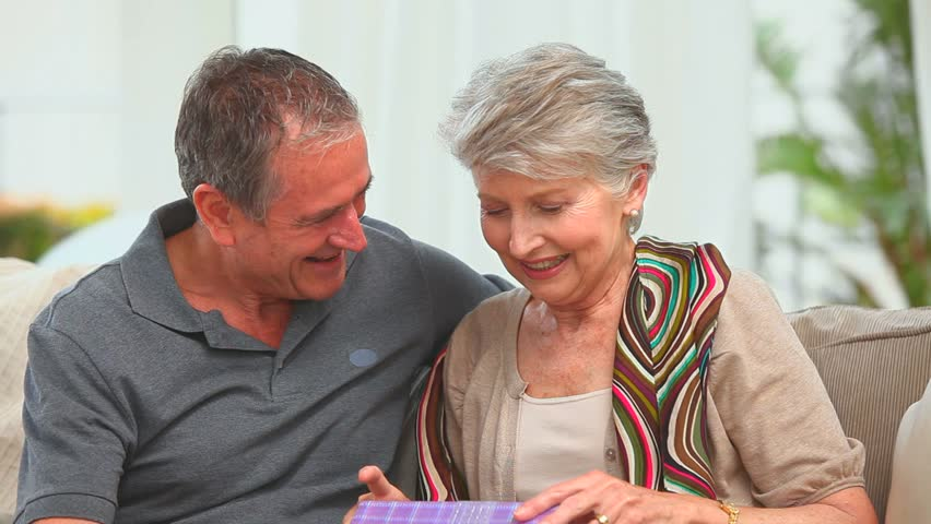 Middle aged couple with a gift looking at the camera in the living room