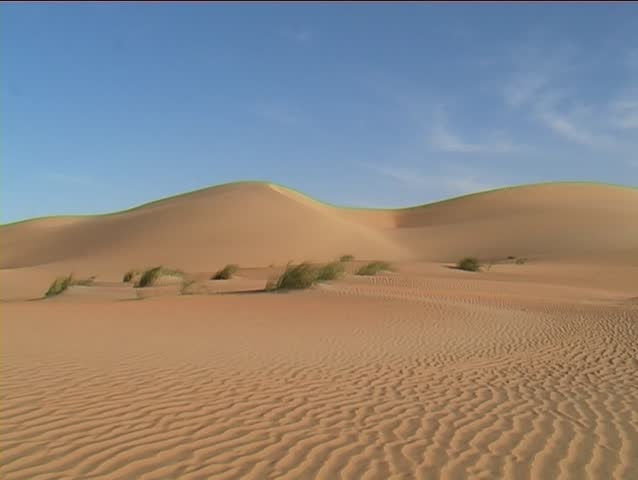 Man climbing a sand dune in the Mauritanian Sahara.
