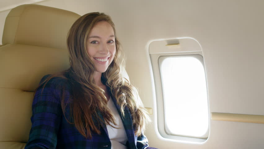 Attractive brunette wearing smart jacket smiles to camera while sitting on an executive jet.  Medium close up, slow motion, originally recorded in 4K at 60fps.
