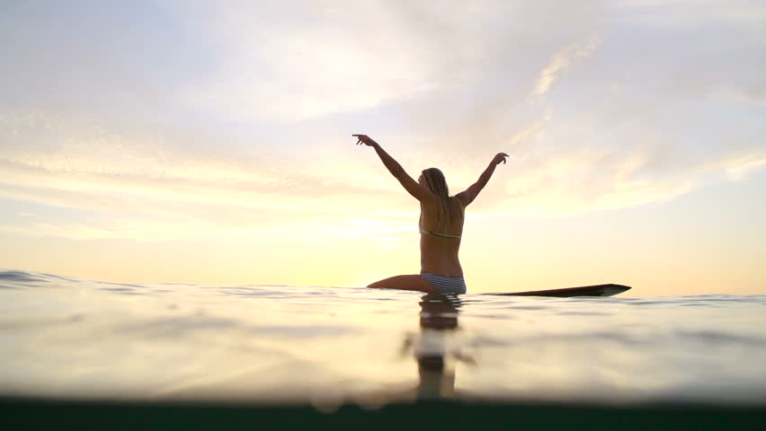 Young Happy Woman Celebrating Success Pose at Sunset on Surfboard.  | Shutterstock HD Video #11233733