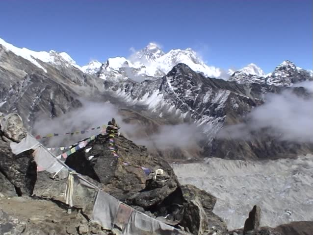 Buddhist prayer flags on Gokyo Ri in Nepal, with Mount Everest towering above in the distance