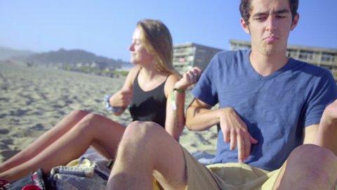 Teens play air guitar at the beach
