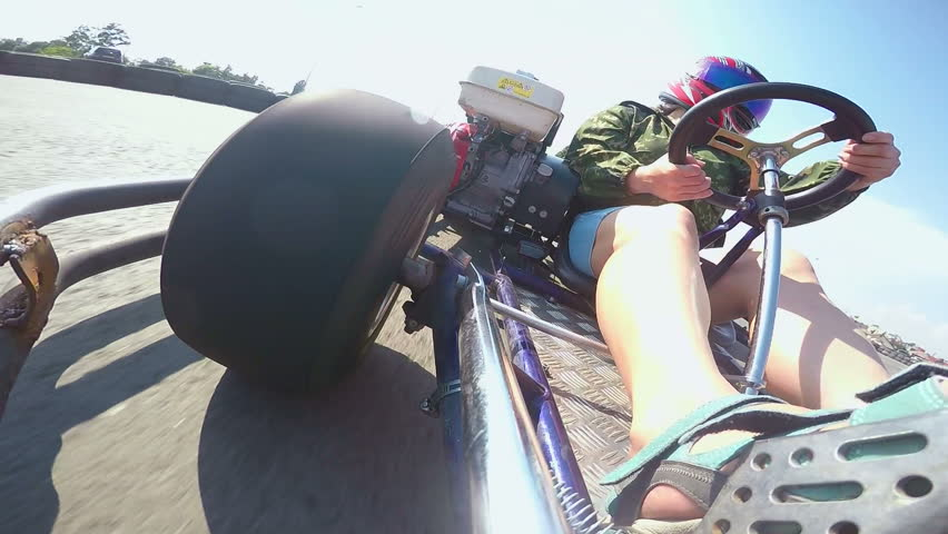 Karting female driver in helmet rushes go-kart on kart track outdoor POV