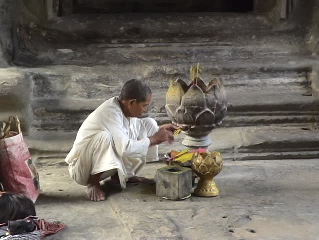 Buddhist nun burning inscence in Angkor Wat temple, Cambodia.