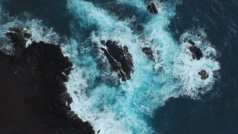 Spinning aerial of the ocean waves washing up on a black basalt rock in Hawaii.