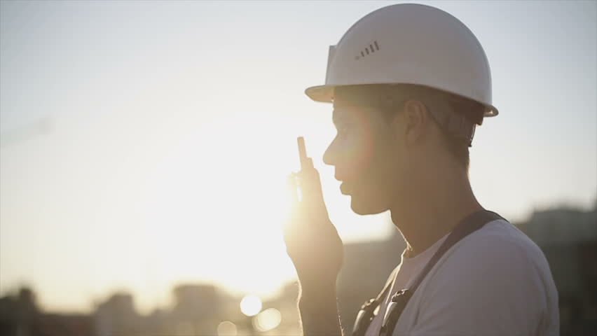 Engineer builder using a walkie talkie giving instructions at a construction site. Sunset time. Slow motion  | Shutterstock HD Video #11311172
