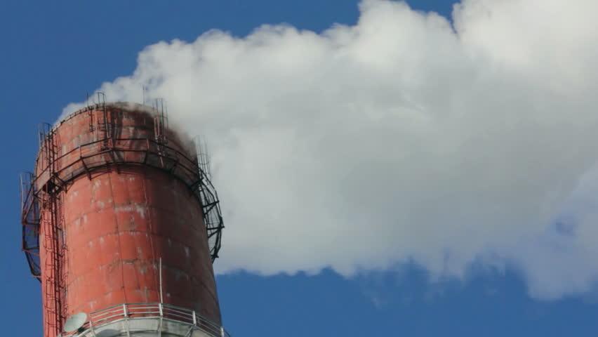 factory chimney with smoke under blue sky - timelapse