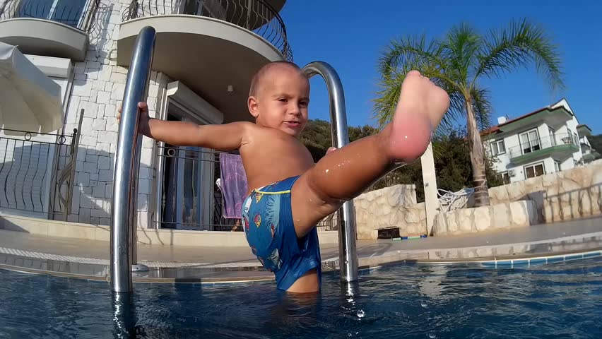 Cute bald toddler wants to get into the swimming pool but scared