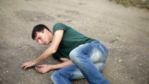 Drunk or sick man falls to the ground from an overdose of drugs or alcohol ill