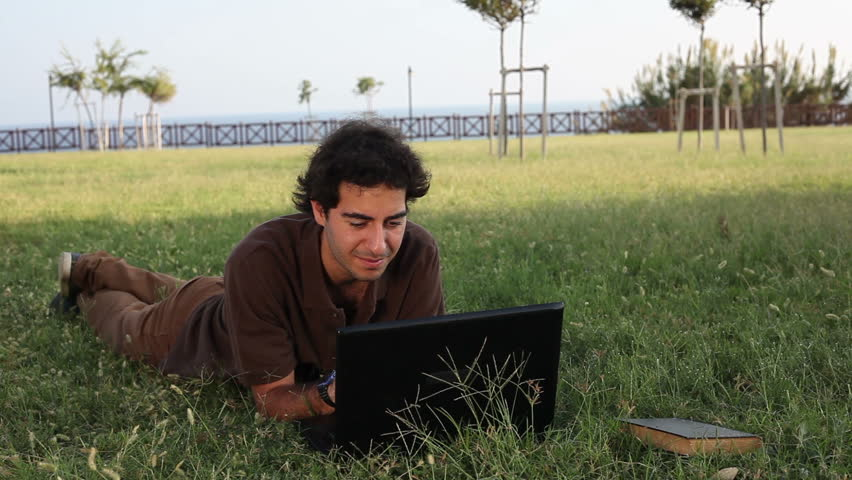 HD: Young adult using his notebook outdoors | Shutterstock HD Video #11394293