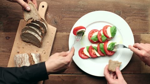 Caprese salad on white plate with bread on cutting board - meal preparation and time-lapse eating on wooden table - stop motion animation