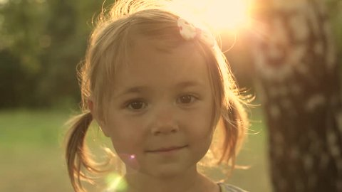 Portrait Adorable Little Girl Smiles outdoor at sunset