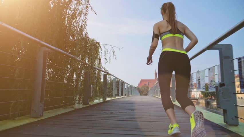 Runner woman running in city exercising outdoors. Steadicam stabilized shot. Sportswoman wearing fitness tracker bracelet and listening to music while training in the city. Slow motion. Lens Flare. | Shutterstock HD Video #11411213