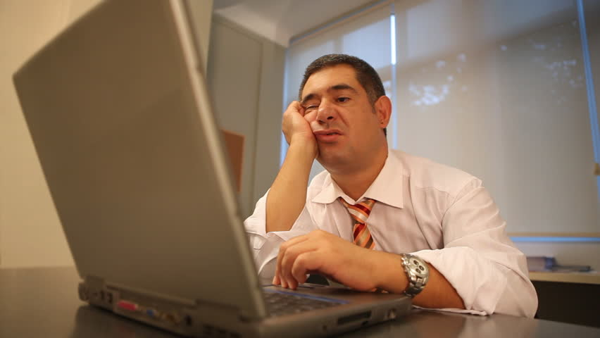 Sleepy businessman using laptop in office - Work - Waiting - Tired - Technology - Business