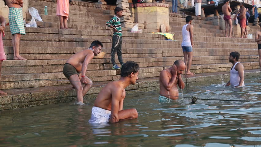 be399b205f7 VARANASI, INDIA - 22 FEBRUARY 2015: Men bathing on the ghats of Ganges river  in Varanasi.
