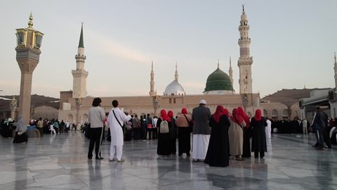 MEDINA, KINGDOM OF SAUDI ARABIA (KSA) - JAN 31 2015: Muslims marching in front of the mosque of the Prophet Muhammad on January 31, 2015 in Medina, KSA. Prophet's tomb is under the green dome.