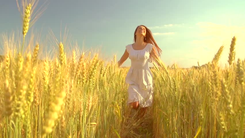 Pretty girl running through yellow wheat field. Happy beautiful young woman outdoors enjoying nature. Free, Freedom concept. Golden Wheat. Slow motion 240 fps. Slowmo. 1080p full HD video footage
