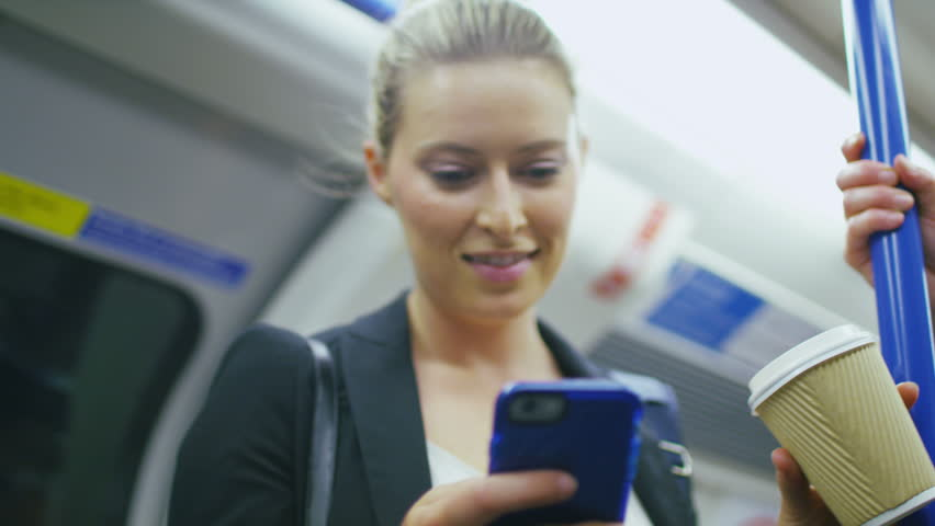 4K Attractive business woman standing on a train drinking from a coffee cup whilst reading her phone, in slow motion, shot on RED EPIC | Shutterstock HD Video #11557823