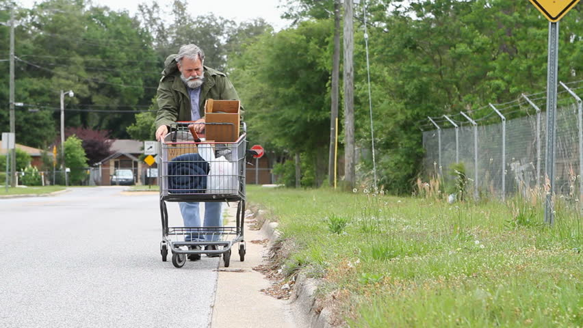 Homeless veteran pushes a shopping cart that holds his belongings down the side of the street.
