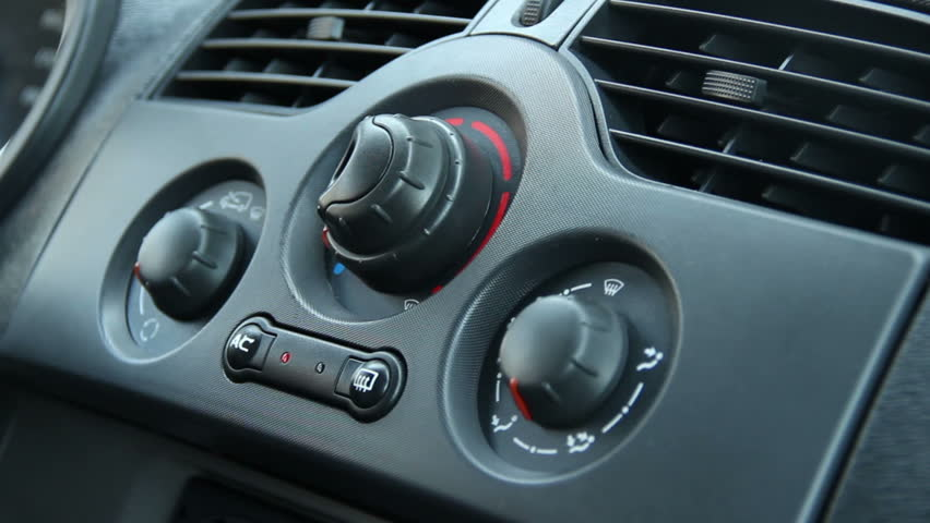 Closeup of Male Turning Heater Switches on Car Defroster