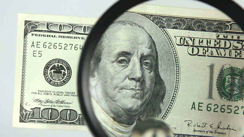Hundred dollar bill inspected to ensure it's not counterfeit, verified as genuine.  | Shutterstock HD Video #1159603
