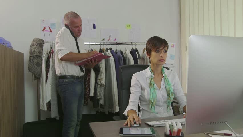 Businesswoman and businessman, woman at work with man as fashion designers, manager in studio working with computer. Team and teamwork with busy colleagues in career situation | Shutterstock HD Video #11631923