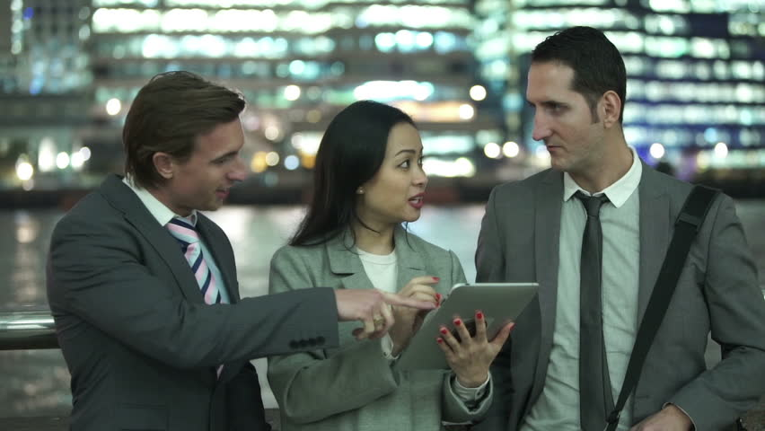 Portrait of attractive young professional group using computer tablet in the city at night. Shot on RED Epic   Shutterstock HD Video #11635463
