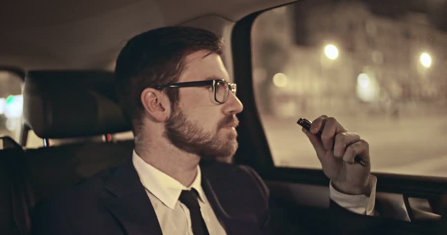 Young manager answering mobile phone in back seat of moving car