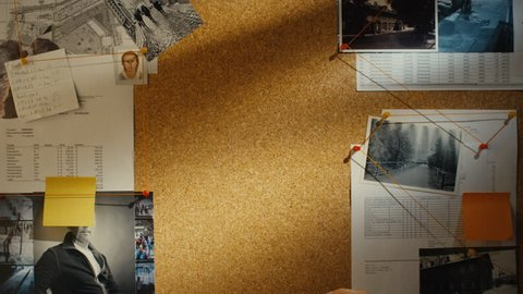 Detective puts a piece of paper on evidence pin board with clues and suspects.