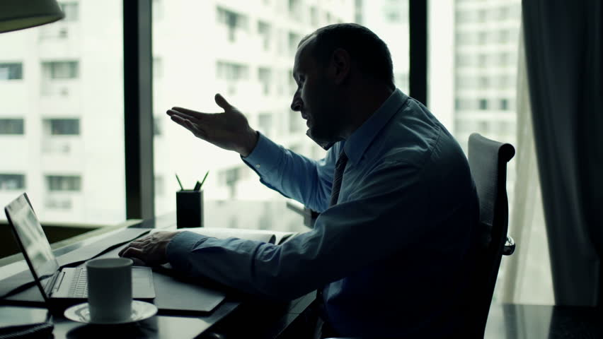 Angry businessman talking on cellphone by desk at office   | Shutterstock HD Video #11744333
