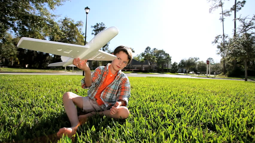Little caucasian boy outdoors playing with toy airplane