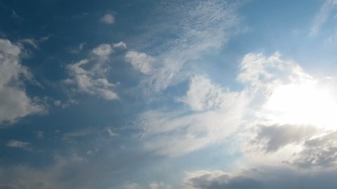 White, rain, gray, haze, dark, black, storm clouds moving across the blue sky against a background of the sun. Time lapse