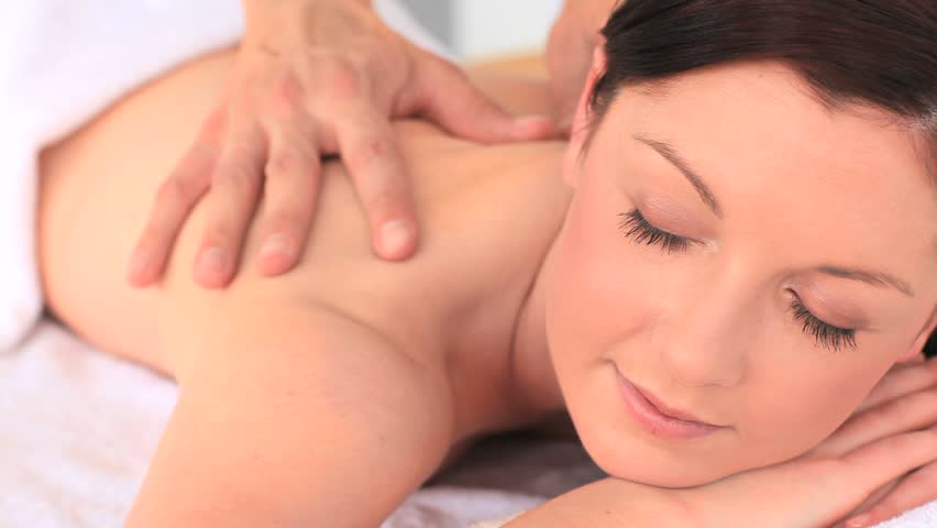 Attractive brunette enjoying a back massage in a Spa centre